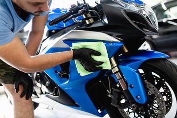 Fototapeta premium Człowiek czyszczenia motocykla z tkaniny. Selektywne skupienie.