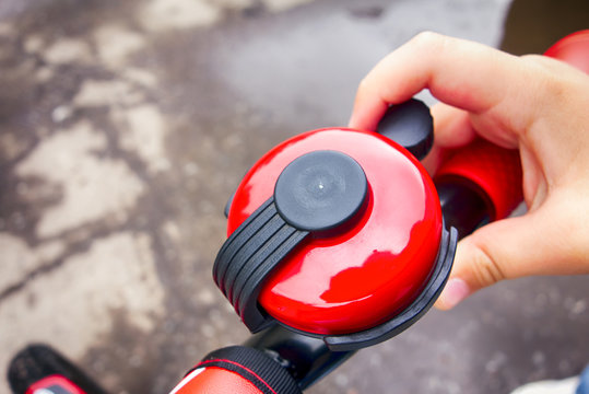 Child hand ringing bicycle bell outside.
