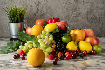 Still life of variery of fruits, oranges, grapes, strawberry, apples berries, cherry, lime and lemons on marble floor