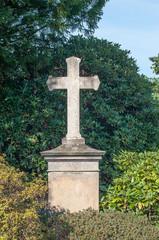 Kreuz-Grabmal auf dem Friedhof von Herdecke vor grünen Hecken aus Rhododendren