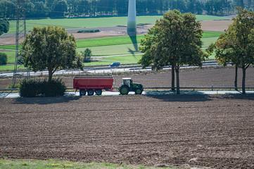 Traktor mit Anhänger auf einer Landstraße zwischen Feldern