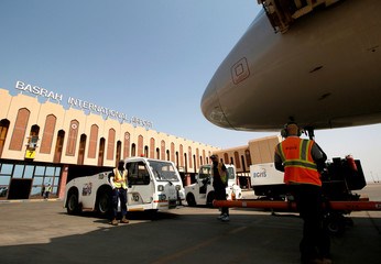 Airport workers are seen at Basra airport after it was targeted by rocket fire in Basra