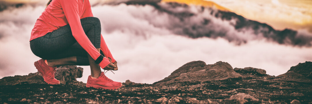 Runner smartwatch woman getting ready for trail run in high cold clouds mountains background tying up running shoes laces. Fitness and sports motivation healthy lifestyle. Banner panoramic crop.