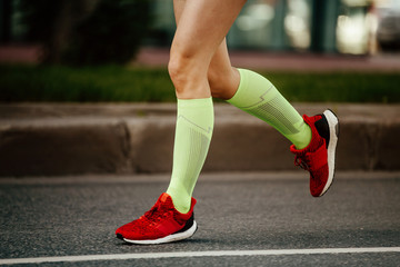 Fototapete - women feet runner in green compression socks and red running shoes