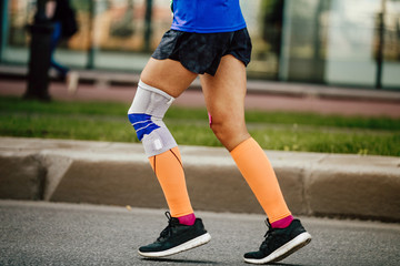 Fototapete - women legs runner in compression socks and kneepad