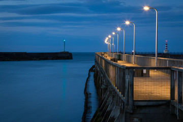 Wooden pier in the fishing village Amble, Northumberland, UK. Evening scene,  footpath illuminated by row of lamp posts. Fototapete