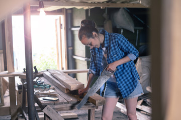 woman engaged in processing wood in the home workshop, carpentry