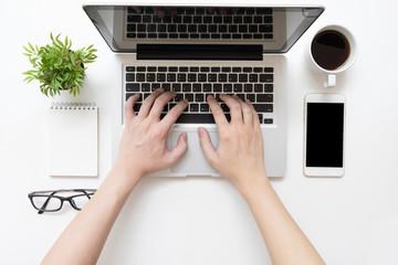 Man is typing on laptop keyboard, top view.