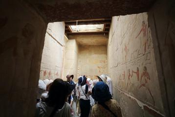 Tourists are seen inside a tomb at Saqqara area near Egypt's Saqqara necropolis, in Giza