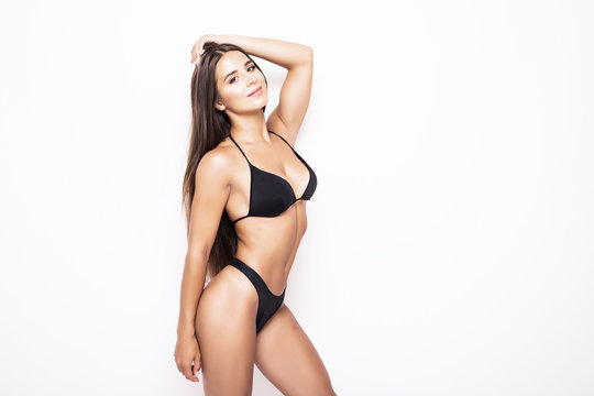 Slim body of young woman in black bikini isolated on white . Girl with healthy sporty figure isolated on white background