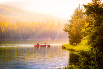 couple in a canoe on a mountain lake during autumn.