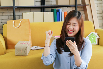 Business start up asian woman is happy with her online order from smartphone .Online selling,e-commerce, shipping theme.