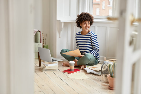 Cheerful African American brocker exams bills, holds brockerage contract, works on distance, uses modern electronic laptop, poses in luxury cozy apartment, notices someone aside. Business activity