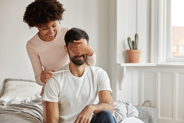 Indoor shot of happy wife makes surprise to husband, covers his eyes and holds pregnancy test, informs he will become father going to share good news, pose together in bedroom. Joyful future parents