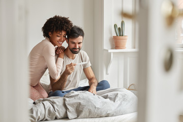 Mixed race family couple rejoice good news in morning, find out about pregnancy, sit together on bed and look happily at control line, have nice relationships. Motherhood and fatherhood concept