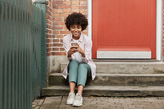 Street style concept. Beautiful curly dark skinned hipster enjoys spare time, sits on threshold of old house, waits for friend outdoor, enjoys online communication via cell phone, connected to wifi
