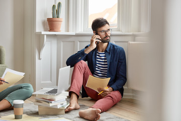 Stylish businessman dressed in fashionable clothes, poses bare foot, examines housing facilities on papers, gives consultancy to partner via cell phone, unrecognizable woman sits near and helps
