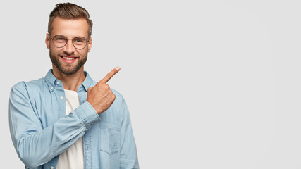 This idea just fascinated me. Attractive young unshaven individual with happy expression, indicates with index finger at blank copy space, advertises you place to vist, isolated over white wall