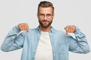 Lets go downstairs. Photo of attractive unshaven man with appealing look, points down with both index fingers, dressed in casual shirt, isolated over white background. Advertisement concept.