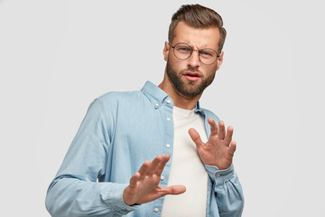 Oh no, dont bother me about this question. Displeased European man makes refusal gesture, keeps hands in front, feels aversion, says its forbidden, dressed in casual clothes, isolated on white