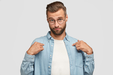 Indoor shot of serious shy European guy points at himself, dressed in casual outfit, wonders to be chosen for participating in conference, advertises his new shirt, isolated over white background