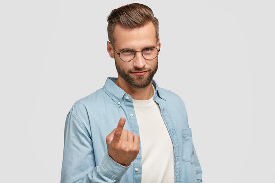 Body language concept. Attractive young man with stylish haircut, looks with appeal at camera, says come here, gestures with index finger, has mysterious expression, isolated on white background