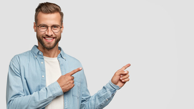 Positive unshaven man looks and points at upper right corner with both index fingers, smiles with approval, suggest going there, sees something positive and very interesting, isolated on white wall