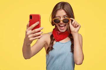 Indoor shot of pleased lovely young teenager blinks eye at smart phone camera, happy to buy new shades, holds modern cell phone, isolated over yellow background. People and modern technology