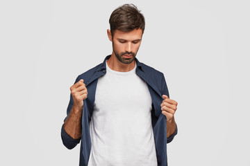 People, clothing and advertisement concept. Confident unshaven young Caucasian man dressed in fashionable shirt, shows blank copy space on white t shirt for your slogan or promotional content.
