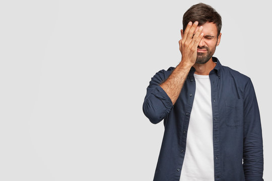 Indoor shot of handsome stressful overworked man covers face with palm, has displeased expression, dressed in casual clothes, poses against white background with copy space for your promotional text