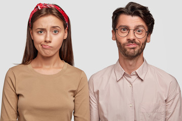 Studio shot of confused students frown faces, purse lips, cant see way out in difficult life situation, stand shoulder to shoulder against white background. Frustrated coworkes recieve task from boss