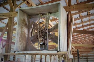 rusted farming fan in an abandoned barn