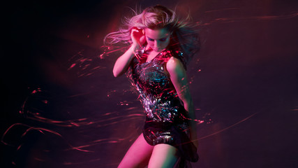 Bright and stylish young woman dancing in club, color light, motion effects Fototapete