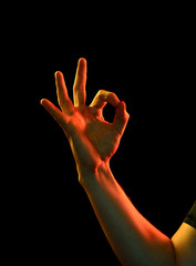 Female hand in ok sign on black isolated background. wp gesture close up in colorful photo lights using flash gels.