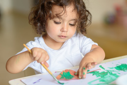 Summer or Autumn.Cute little girl drawing with green paint on fall lives. Curly adorable child painting at table.