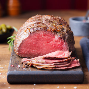Roast beef on cutting board. Wooden background.