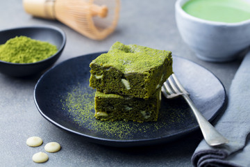 Matcha green tea cake, bars, brownie with white chocolate on a plate. Grey background.