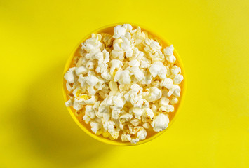Movie theater popcorn in a bowl on yellow background. Top view