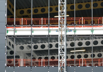 detail of the construction site of a metal framed large building development with a hoist running up the outside and safety fencing with structural steel girders and floors visible