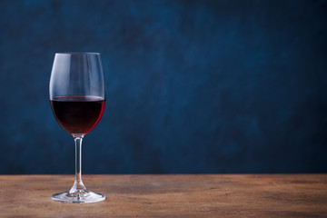 Glass of red wine on wooden table. Blue background. Copy space.