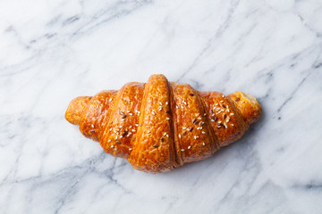 Croissant on marble table. French traditional pastry. Top view.