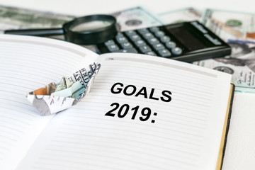 2019 goals text in open notebook with dollar banknote origami ship and calculator, money and magnifier in the background. Business financial  Concept