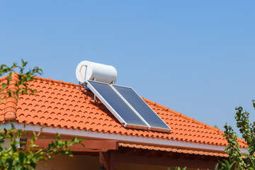 Solar water heating panel and water collector on a house roof.