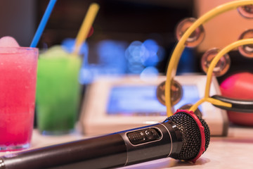 Black microphone in karaoke club, with remote controller, melon and strawberry soda drinks, yellow tambourine and screen for singing music on stage party.