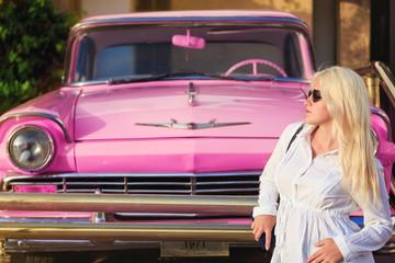 young pretty girl near pink retro car