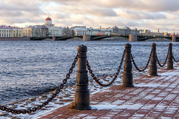 Fencing from cast-iron pillars and chains on the river embankment in the European city on a winter evening.