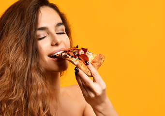 Young beautiful woman eat slice of pepperoni pizza with closed eyes smiling on yellow