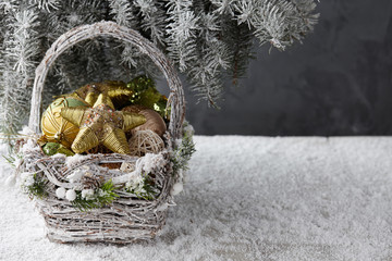 Wicker basket with Christmas gifts, toys and holiday decorations under snowy fir tree, copy space