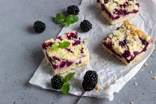 Cheesecake bars with blackberries and streusel with mint leaves on a white baking paper.