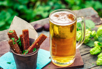 Beer with garlic rye croutons on table in garden outdoors